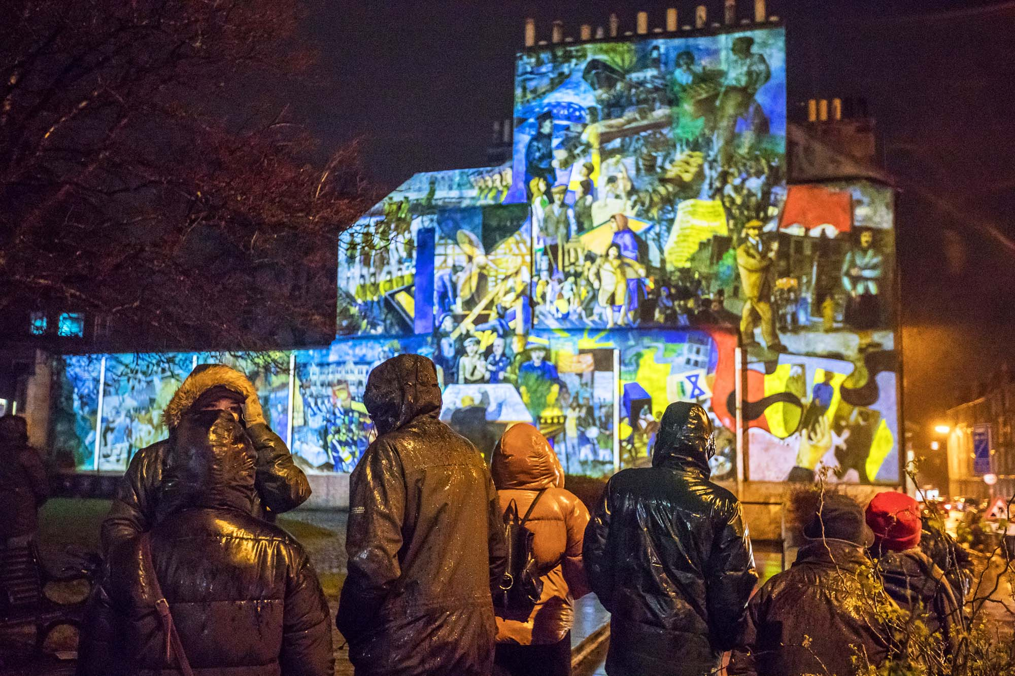 audience standing in front of leith mural projection
