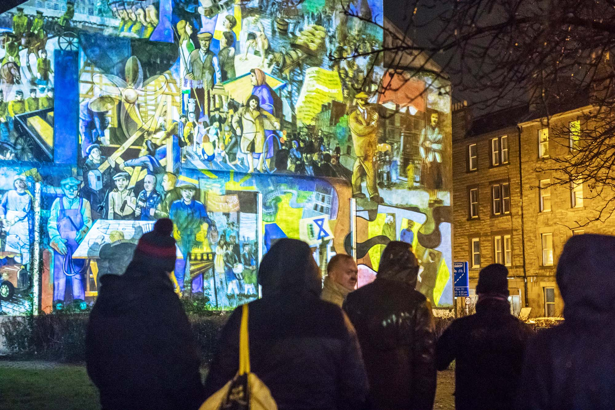 crowd standing in front of leith mural projection