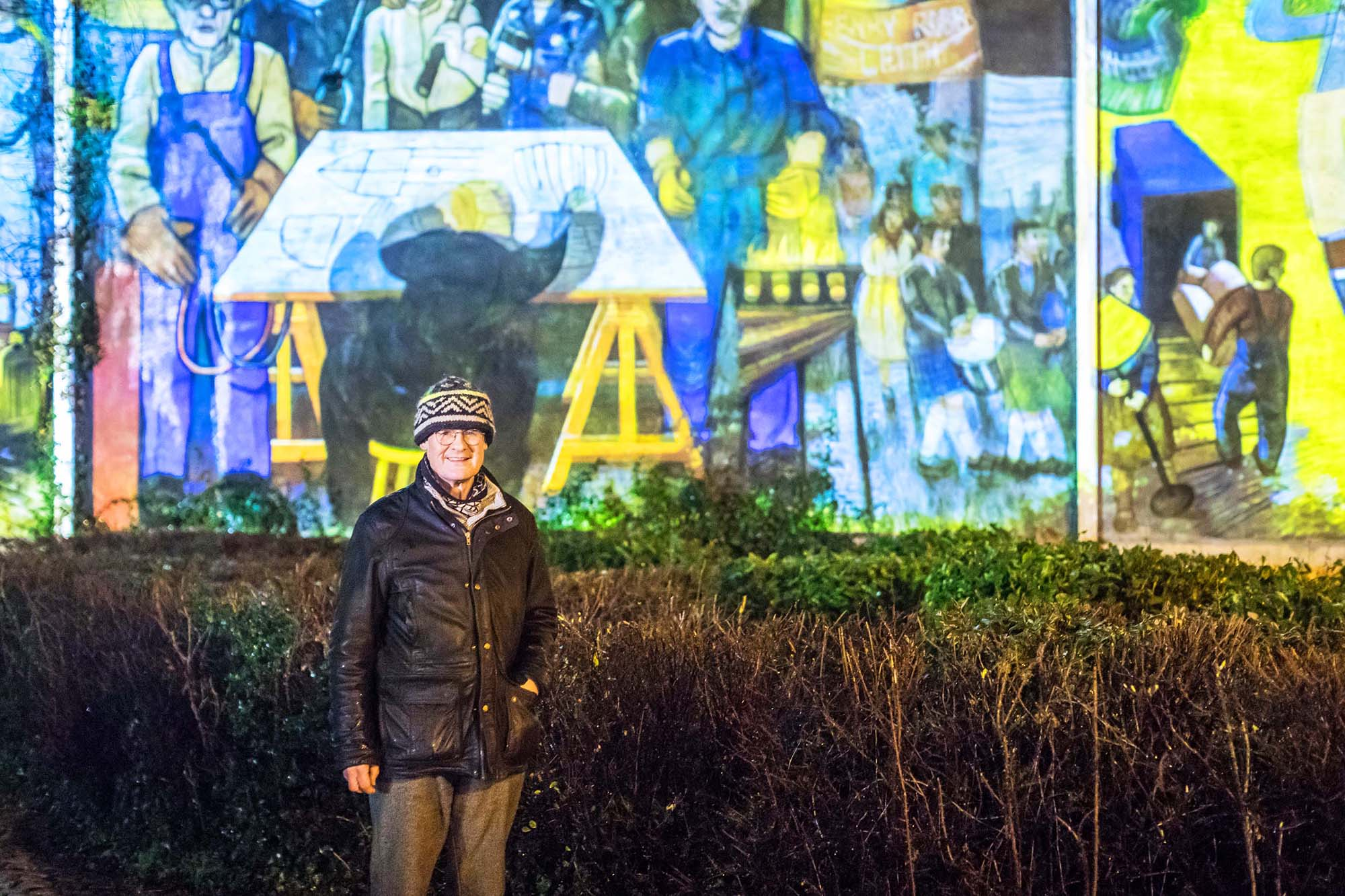man standing in front of leith mural projection